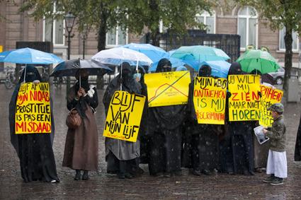 Femke Halsema - uiterst links met de blauwe paraplu - doet anoniem mee aan een demonstratie voor islamitische vrouwen-rechten
