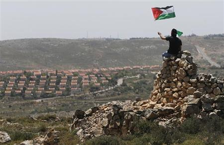 A protester waves a Palestinian flag in front of the Jewish settlement of Ofra during clashes near the West Bank village of (April 26, 2013. REUTERS/Mohamed Torokman)