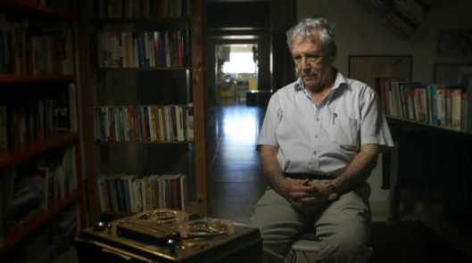 """Amos Oz, """"is one of the aging stars of Censored Voices: a photo of him posed before a tape recorder, listening to his own testimony, was spread over three columns in the New York Times""""."""
