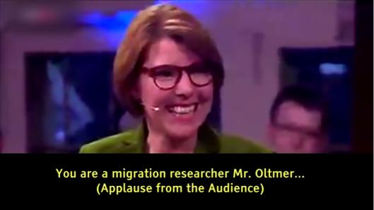 De presentatrice glundert en het publiek klapt klaterend