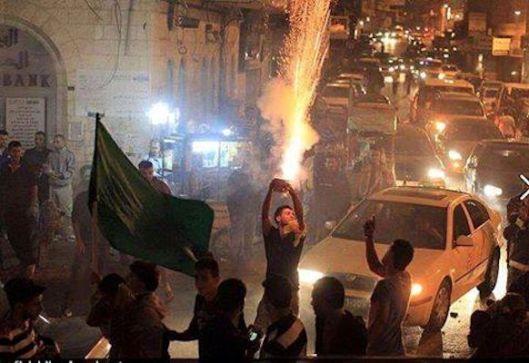 Hebron, Judea, woensdagavond, 8 juni 2016. Overal vieren de Palestijnen feest wanneer het nieuws bekend raakt dat vier Joden werden geëxecuteerd in een restaurant in Tel Aviv. Palestijnen komen overal de straat op, claxonerende auto's, schieten vuurwerk af, dansende en joelende Palestijnen bezetten de straten, koekjes en andere snoepjes worden gul uitgedeeld aan voorbijgangers bij wijze van feest telkens wanneer willekeurig Joden worden vermoord [beeldbron: Ynet News/The Israel Project].