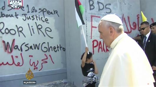 """Paus Francis nadert de afscheidingsmuur in de buurt van Bethlehem, op 25 mei 2014, waarop graffiti met de vergelijking van Palestijnen met de Joden als de Nazi's: """"Bethlehem ziet eruit als het Getto van Warschau."""" Zo ja, dan ziet het er alleen op die manier uit, omdat de stad Bethlehem met een christelijke meerderheid in 1995 werd overgedragen aan de totale controle door de Palestijnse Autoriteit, en de meeste belegerde christenen zijn gevlucht als gevolg van de islamitische vervolging. (Afbeeldingsbron: Al Jazeera video screenshot)"""